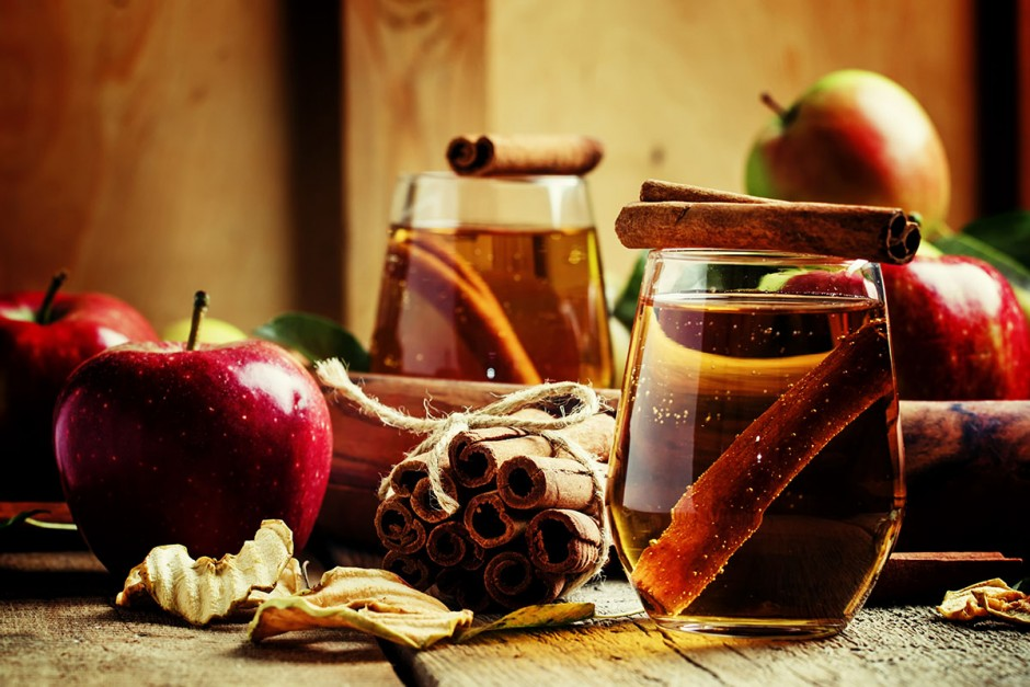 Apple juice with cinnamon in a glass and fresh apples on a vinta